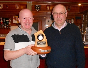 Ardrossan Castle winning skip Andrew Campbell receives the trophy from ICA President Bill Gray.